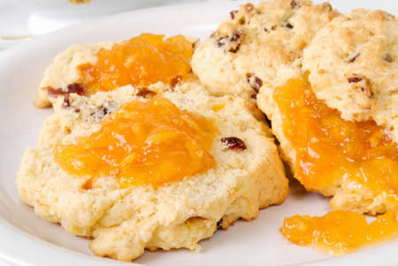 Homemade fruit scones covered with orange marmalade preserves and served on a white plate.