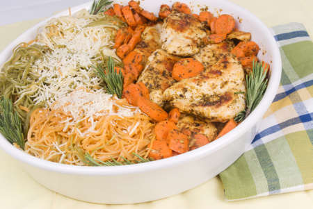 Homemade chicken parmesan with three varieties of pasta, sliced carrots and with fresh rosemary served in a white ceramic baking dish.