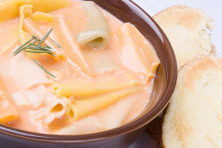 Homemade rainbow pasta and tomato soup served in a brown bowl with toasted bread on the side. Stock Photo