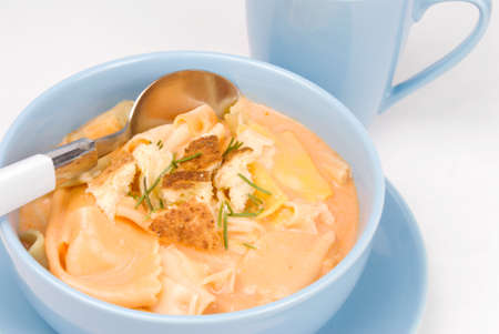 Homemade tomato soup made with rainbow bow tie pasta and served in a blue bowl. Stock Photo