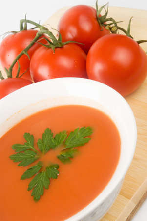 bowl of tomato soup with flat leaf Italian parsley for a garnishment. A bunch of vine ripe tomatoes with stems are in the background. The soup is served on a wooden cutting board.