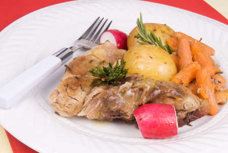 homemade ale-sauced country style pork ribs served with whole gold potatoes, baby carrots, and radishes in a savory ale sauce. Rosemary sprigs are used for garnishment. Stock Photo