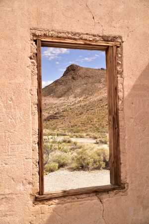 Artfully framed mountain in window of ghost town jail in Ryholite