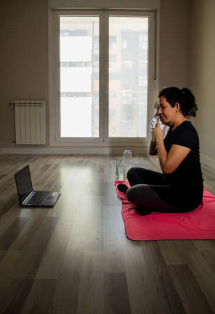Caucasian girl doing yoga in her living room with a laptop