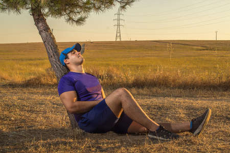 Caucasian young man with sportswear purple shirt blue pants and a cap resting on a tree after running.