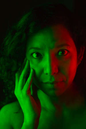 Selective focus portrait of young caucasian woman with green and red lights on his face