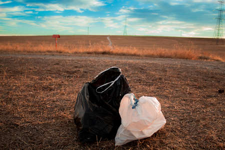 Garbage bags in the clean forest with a sunset in the background Stock Photo