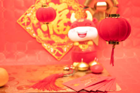 Chinese New Year arrangement with table and red background with red and silver decorations, tablecloths and tangerines an ox