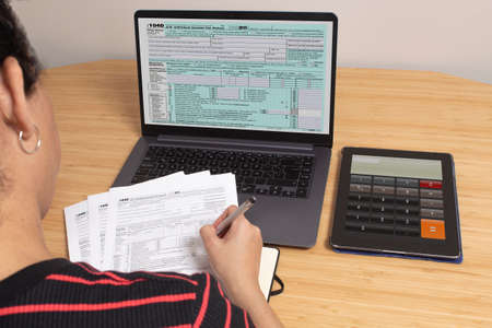 Session to set up bills and bills for tax day at a table with a calculator and a laptop with a spreadsheet