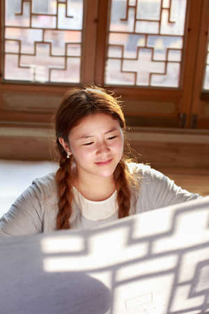 lattice window: A Chinese girl sitting in a traditional lattice window to see Chinese painting, Stock Photo