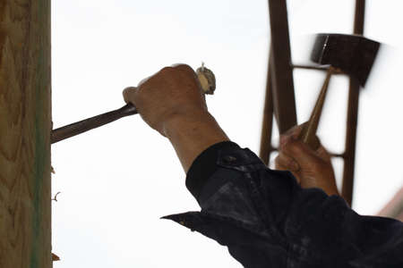 knock: A worker is holding a tool to knock on wood,