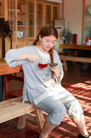 irradiation: A girl dressed in traditional clothing sitting on wooden benches  is drinking tea