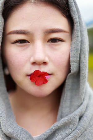 imitate: An oriental girl with a red flower in her mouth, the head wrapped in a scarf to imitate the style of Arabia,