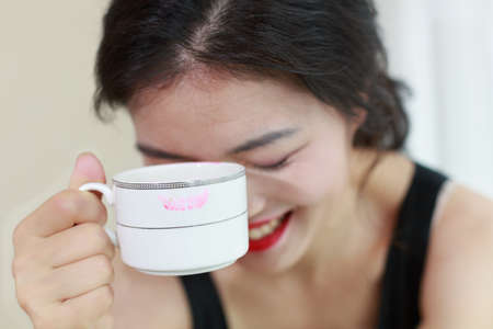 bowed head: A happy Asian woman with a cup of coffee Stock Photo