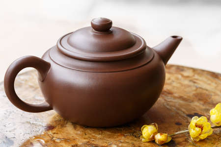enameled: A dark-red enameled pottery teapot Stock Photo