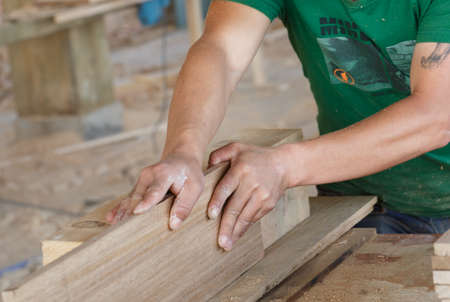 hands work: A pair of powerful arms, the craftsman is planing wood,