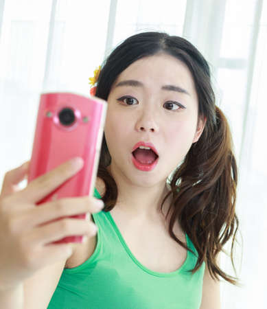 An Asian girl with a pink mobile phone Stock fotó - 59374378
