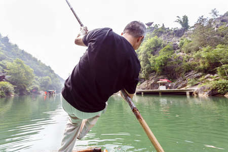 punting: A man with a bamboo pole in punting