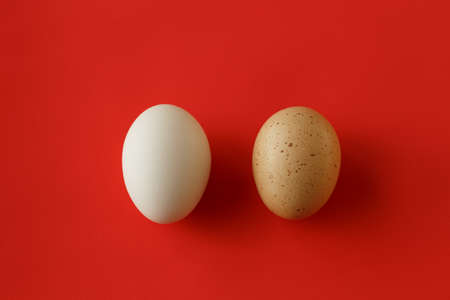 An egg with a yellow brown spot and a clean white egg on the red background