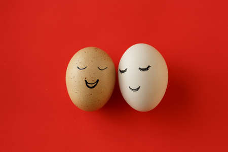 Two eggs with a joyous expression on the red background 版權商用圖片