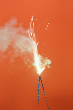 Two burning fireworks in the orange background
