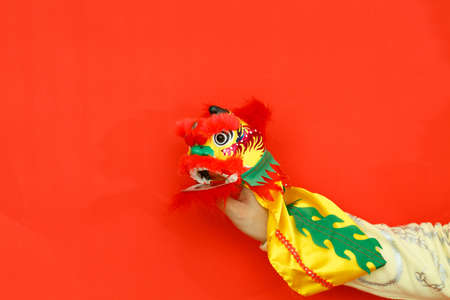 A hand manipulated Chinese style tiger puppets on the red background