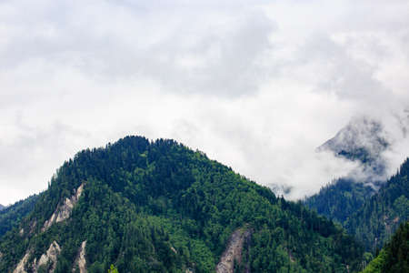 Peaks and green forests are among the white clouds. Reklamní fotografie