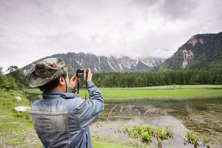 A man holds a camera to record plateau scenery Imagens