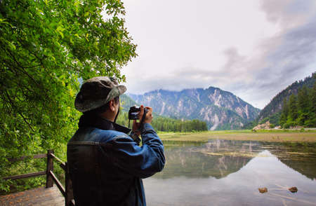 A man holds a camera to record plateau scenery Reklamní fotografie