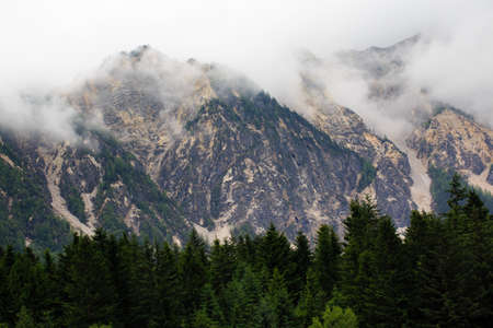 Peaks and green forests are among the white clouds. Imagens