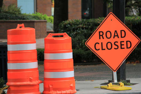 A horizontal image of orange plastic barrels and a road closed sign to protect workers during road construction.