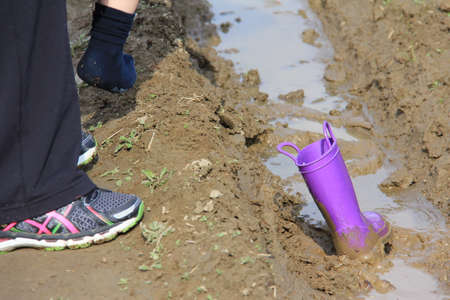 A purple  rubber boot stuck in the mud.