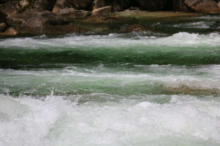 A mountain stream in full spring runoff, with white water sections, that is dangerous in spring.