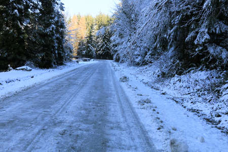A horizontal image of a plowed country road in winter.