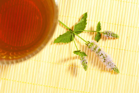 tea and fresh peppermint flowers on bamboo, top view photo
