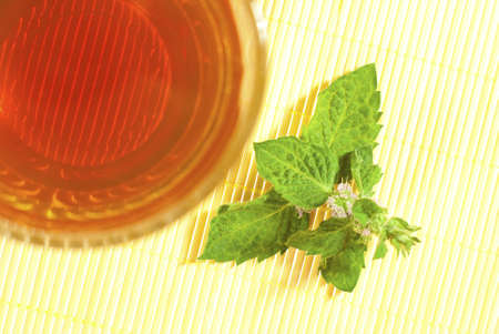 tea and fresh mint flower on bamboo, top view photo