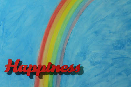 Red letters spelling the word happiness to illustrate the concept of joy, happy, love and wellness; landscape format. Stock Photo