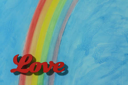 The word love with a background rainbow, illustrating the concept of love, lust, desire and joy in a landscape format. Stock Photo