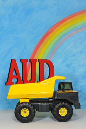 apalancamiento: The letters AUD, Australian dollar symbol, in the back of a mining truck, against a blue sky, representing the strength and weakness of the Australian currency which is a resource currency reliant on mining. Foto de archivo