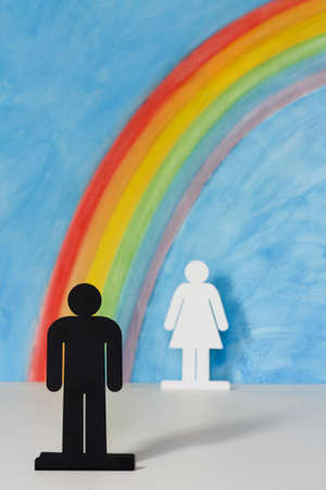Man and women icons with a rainbow and blue sky to illustrate the concept of male, female and sexual discrimination Stock Photo