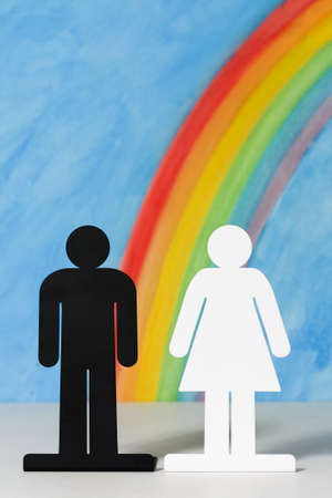 Man and women icons with a rainbow and blue sky to illustrate the concept of male, female and gender