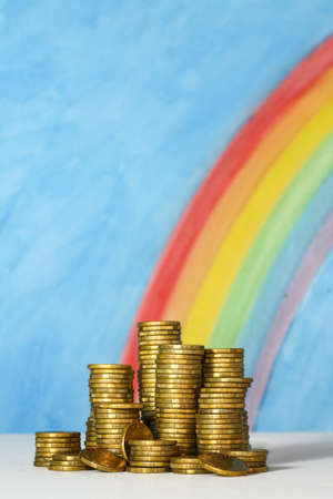 Gold coins against a blue sky and rainbow background, representing the pot of gold at the end of the rainbow. Stock Photo