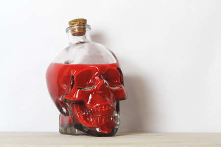 Human skull containing blood or poison, a symbol of death, horror and vanitas.