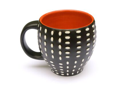 A coffee mug which is dotted on the outside and red on the inside. White background. photo