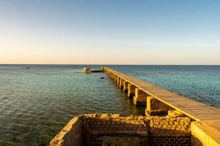 Old wooden pier (jetty) of the Sanganeb Reef Lighthouse near Port Sudan, on the Red Sea, in Sanganeb National Park, with endless horizon sea view during golden hour sunset. Stockfoto