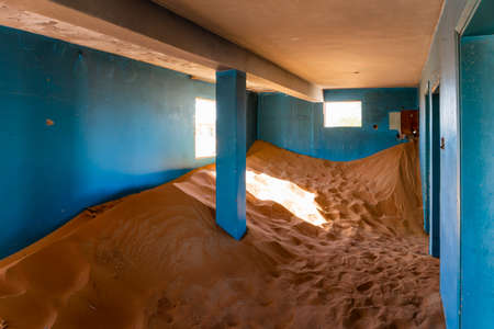 Neglected house interior with blue walls buried in the sand in Al Madam ghost village in United Arab Emirates.
