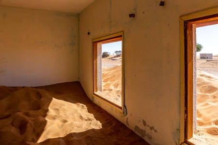 Neglected house interior buried in the sand in Al Madam ghost village in United Arab Emirates. Фото со стока
