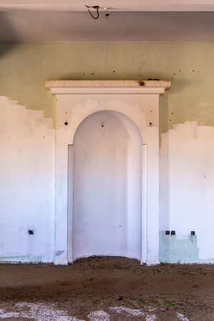 Demolished old mosque interior with qibla wall - mirhab (niche) in ghost village Al Madam in Sharjah, United Arab Emirates.