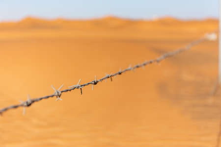 Single barbed wire with desert dunes in the background in Al Madam ghost village, United Arab Emirates.