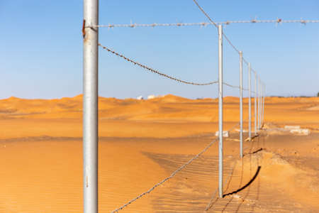 Barbed wire fence with desert dunes and blue sky in the background in Al Madam ghost village, United Arab Emirates, fence of the old mosque.